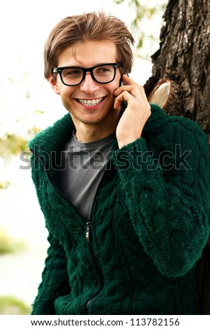 Young and handsome guy with cellphone in the autumn park - stock photo