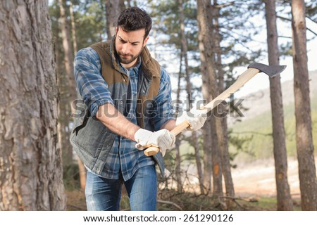 Young and handsome lumberjack man swinging an axe in the forest and cutting down the trees - stock photo