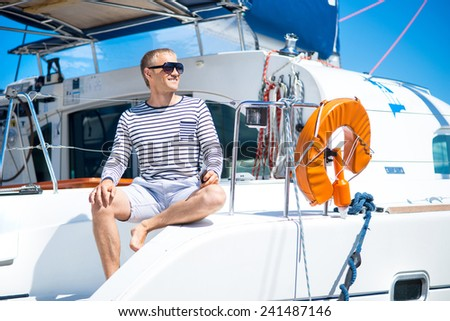 Young and handsome man on a sailing boat - stock photo