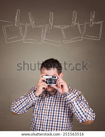 Young and handsome photographer man taking a picture with old retro (vintage) camera on old brown wall background with empty photo frames with place for your text or drawing - stock photo
