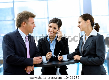 Young and happy business people standing around coffee table, drinking coffee and talking, smiling, indoor.