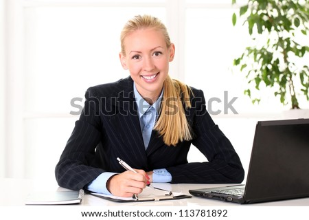 Young and happy businesswoman is working at the office - stock photo
