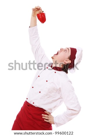 Young  and happy chef with red paprika - stock photo