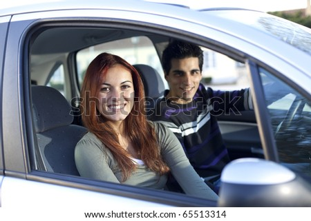 Young and happy couple inside a land vehicle for the begin of a long travel (selective focus with shallow DOF) - stock photo