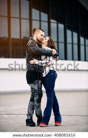 Young and happy couple relaxing in the city and kiss - stock photo