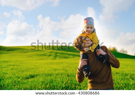 Young and happy father walks across the field with his son at sunset in the summer. The concept of family - stock photo