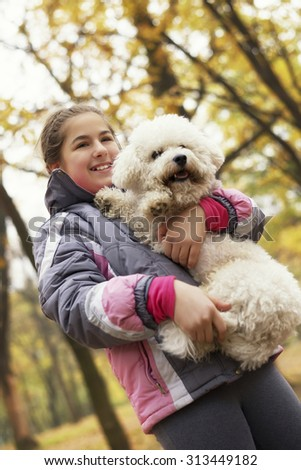 Young and happy girl holding her dog (Bichon Frise) and enjoying outdoor in a beautiful autumn day. Look from below.