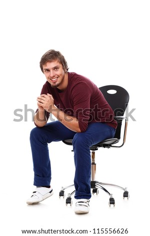 Young and happy guy sitting on the chair over white background - stock photo