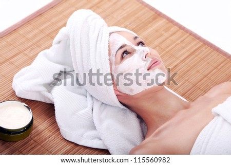 Young and happy woman relaxing with facial mask - stock photo