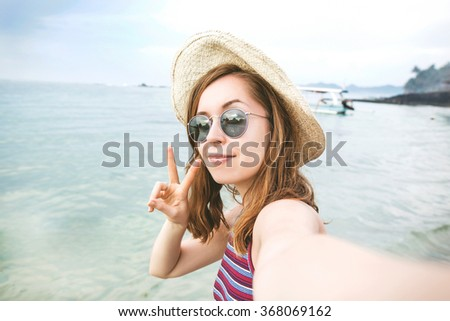 Young and happy woman tourist takes selfie self portrait photo on a beach of Bali, Indonesia while vacation - stock photo
