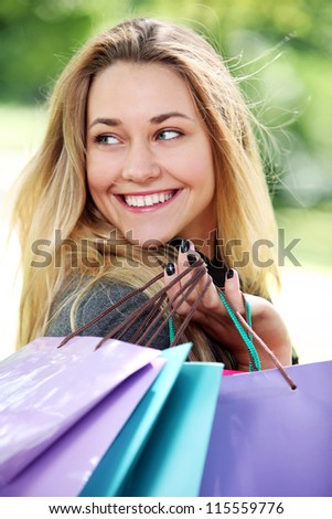 Young and happy woman with shopping bags in the park