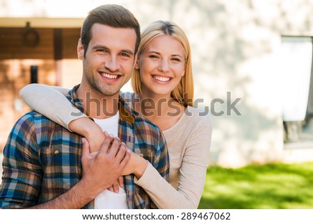Young and in love. Beautiful young couple bonding to each other and smiling while standing against their new house  - stock photo