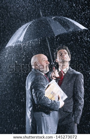 Young and middle aged businessmen watching rain from under umbrella - stock photo