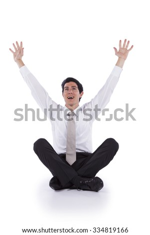 Young and modern businessman sitting on the floor with his arms up (isolated on white) - stock photo