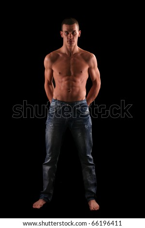 young and muscular warrior posing in front black background - stock photo