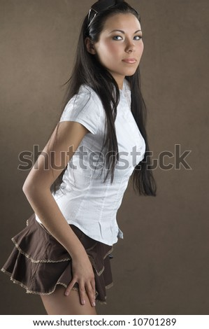 young and nice girl with white shirt and brown short skirt