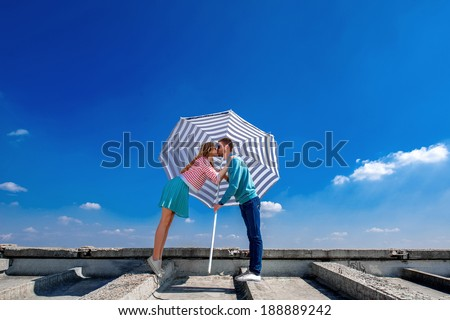 Young and pretty couple kissing on the roof under the umbrella on the blue sky background - stock photo