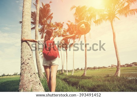 Young and pretty girl with outspread hands enjoying holidays in nature resort (intentional sun glare and vintage color)  - stock photo