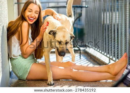 Young and pretty woman playing with her white dog on the balcony - stock photo