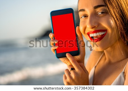 Young and pretty woman showing smartphone with white screen outside on the beautiful rocky seacoast. background. Close-up view with woman's toothy smile - stock photo