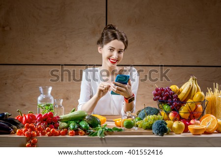 Young and pretty woman using smart phone sitting at the table full of fruits and vegetables in the wooden interior. Counting calories with mobile app. Food and health care concept - stock photo