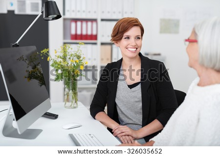 Young and Senior Businesswomen Talking at the Table Inside the Office. - stock photo