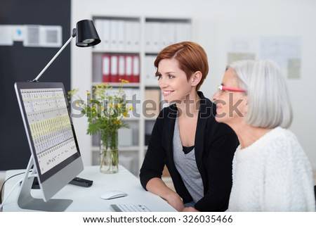 Young and Senior Office Women Working on the Computer Inside the Office. - stock photo