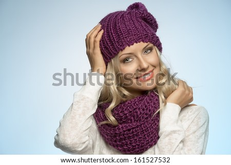 young and sexy blond girl wearing purple scarf and hat in winter dress on light blue background