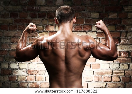 Young and sexy guy with muscular body against a brick wall - stock photo