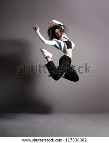 Young and sexy modern dancer over grey background - stock photo