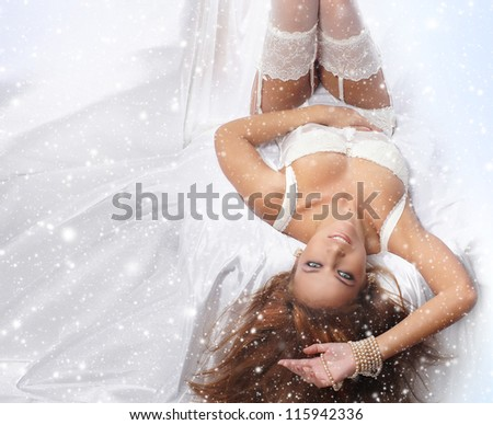 Young and sexy redhead woman in white lingerie over snowy background - stock photo
