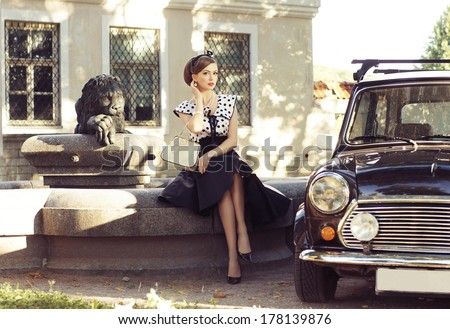 Young and sexy woman with her car - retro style image. - stock photo