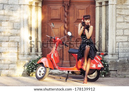 Young and sexy woman with her motor scooter - vintage style image. - stock photo