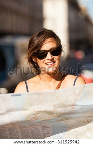 Young and smiling woman consulting a map in the street. Close up - stock photo