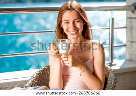 Young and smiling woman drinking milk on the balcony on blue water background - stock photo