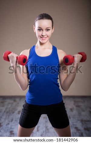 Young and strong girl doing exercise: lifting dumbbells for biceps standing. - stock photo