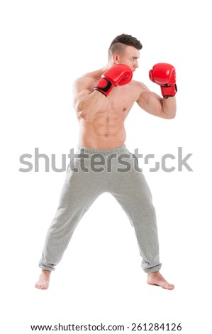 Young and strong, muscular guy wearing red boxing gloves and sporty pants on white background - stock photo