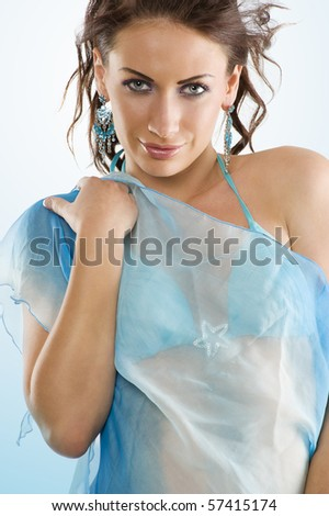 young and stunning brunette wearing a sky-blue swimsuit with scarf and hairstyle