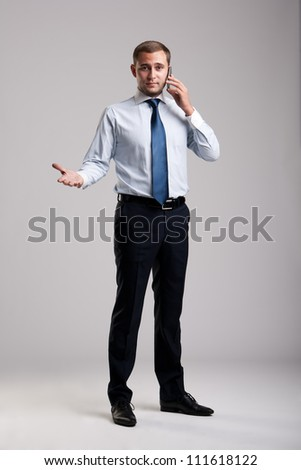 Young and successful businessman holding a smartphone - stock photo