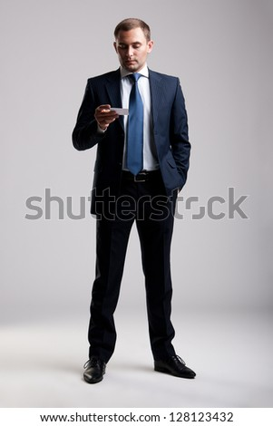 Young and successful businessman looking at business card