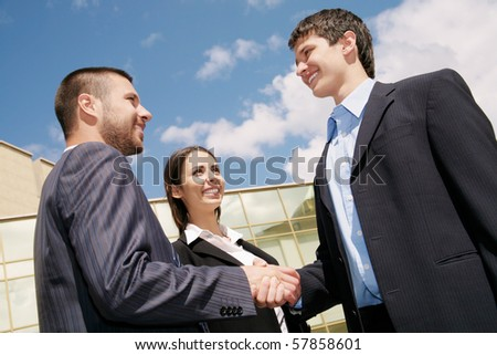 Young and successful businesspeople shake hands against the sky - stock photo