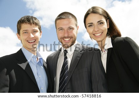 Young and successful businesspeople stand against the blue sky - stock photo