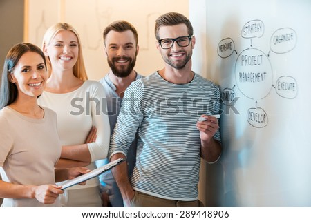 Young and successful team. Group of cheerful young business people in smart casual wear looking at camera and smiling while standing together near whiteboard  - stock photo