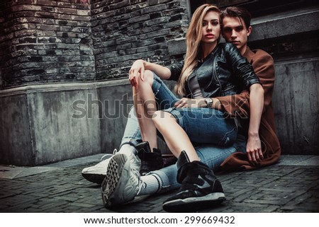 Young and trendy man and woman sitting on the street with brick walls. Fashion style - stock photo