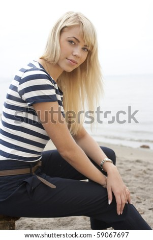 Young and very attractive blonde woman enjoys the sea side