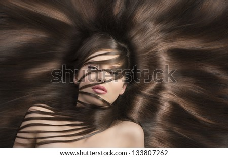 young and very nice woman  with long  hair laying down and some locks on the face and the neck - stock photo