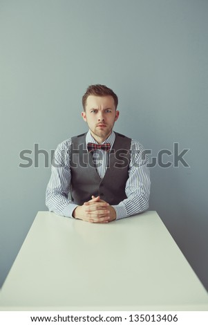 Young angry business man in bowtie and jacket sitting at the table - stock photo
