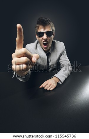 Young angry businessman boss is pointing his finger and screaming - stock photo