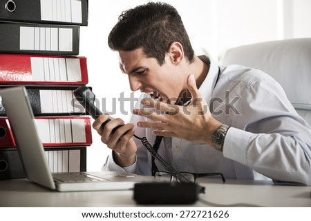 Young Angry Businessman sitting in the office and screaming on the phone. - stock photo