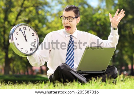 Young angry businessperson with computer sitting on grass and looking at clock in a parK - stock photo